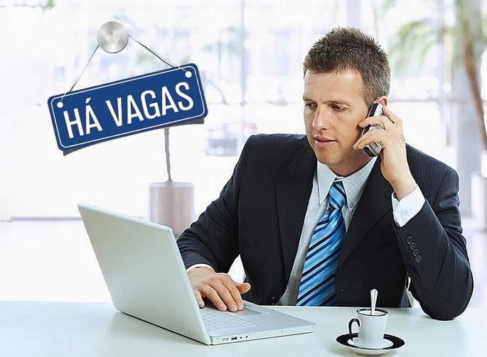 homem de terno utilizando notebook e telefone